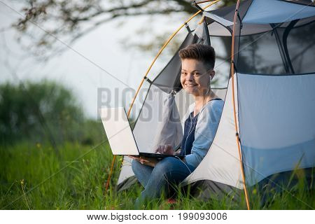 Beautiful Young Woman Smiling To The Camera Joyfully Sitting In A Tent While Camping Using Her Lapto