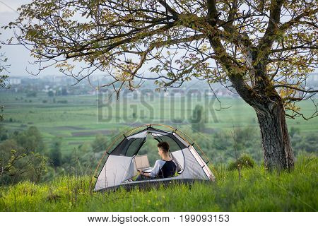 Young Woman Sitting In A Tent On Top Of A Hill Using Her Laptop While Camping Lifestyle Active Onlin