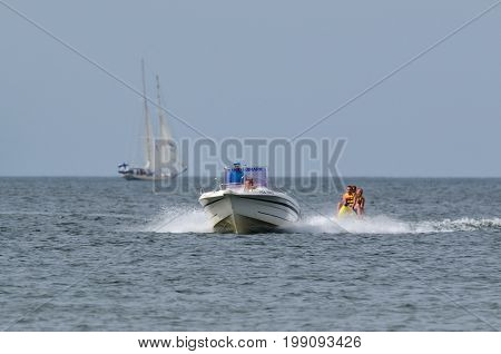 BALTIC SEA / POLAND: Beach holiday. Ride the tourists floating banana by the sea