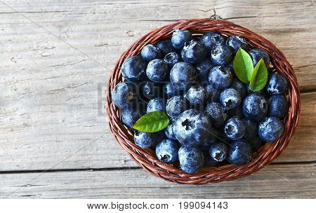 Freshly picked blueberries in a basket on old wooden background.Fresh blueberries with green leaves on rustic table.Blueberry.Bilberries.Healthy eating,diet and nutrition concept.