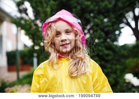 Happy little child girl in yellow raincoat
