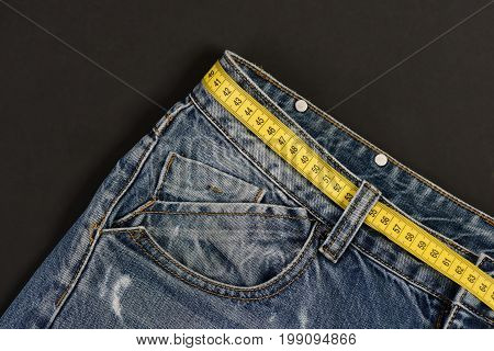 Close up of jeans belt loops and pocket. Jeans with yellow measure tape instead of belt. Top part of denim trousers isolated on black background. Healthy lifestyle and dieting concept.