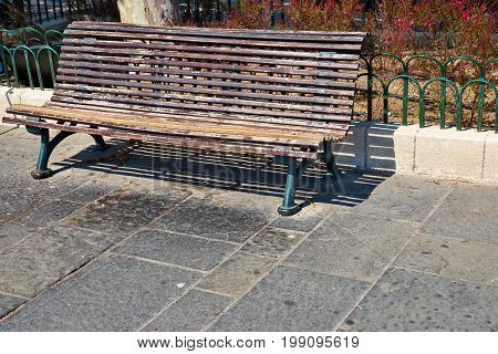 one old wooden bench for rest in the square and untidy garbage nearby