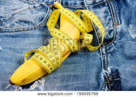 Health and male sexuality concept. Mens denim pants crotch with banana imitating male genitals. Banana wrapped with yellow measure tape on jeans selective focus. Jeans zipper and pocket close up.
