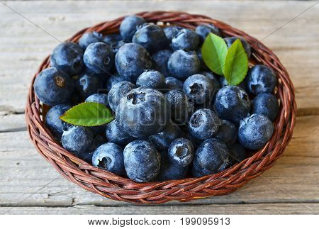 Freshly picked blueberries in a basket on old wooden background.Fresh blueberries with green leaves on rustic table.Blueberry.Bilberry.Healthy eating,diet and nutrition concept.