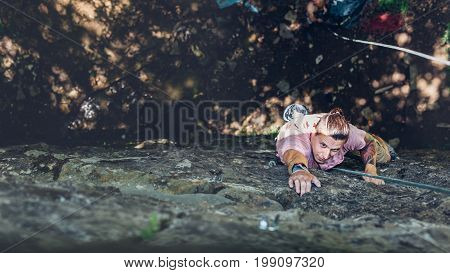 Young Man Climbing On A Wall Top View. Extreme Lifestyle Outdoor Activity Concept