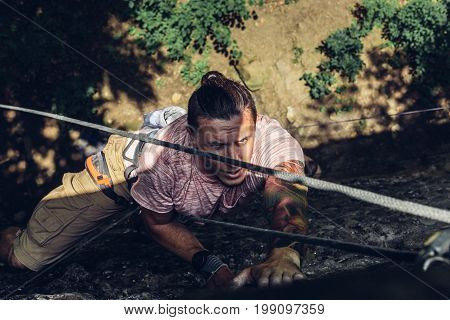 Concentrated Man Climber Climbs A Steep Cliff. Extreme Lifestyle Outdoor Activity Concept