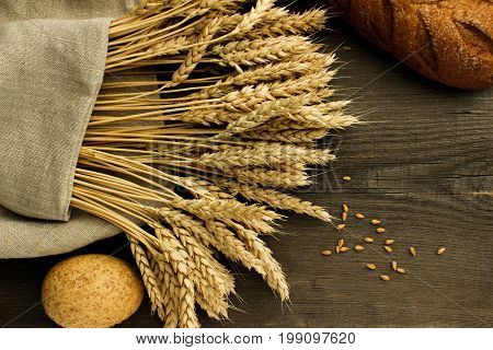 Bakery products in a linen napkin on a wooden surface and in a wicker basket, close-up. View from above.