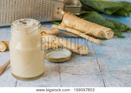 Fresh horseradish root, a small jar with seasoning and a metal grater on an old wooden table. Used in cooking.