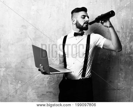 Man with dark beard in white shirt suspenders and red bow tie drinks wine and holds laptop on beige background