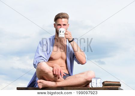 Adult handsome man in fashionable shirt. Sexy energized young macho holding cup of tea. Bearded guy enjoy healthy morning. Start of the day with coffee. Male model posing against the sky. poster