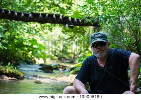 Handsome caucasian communist man with gray beard with cap with red star sitting on the riverside with blue clear water and green forest and wooden bridge in the background