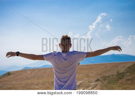Handsome young caucasian blonde guy happy man with reflective black sunglasses widen arms from the back. Grass field in the summer with mountains and blue sky and clouds in the background