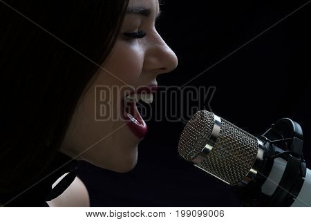 Singer in front of a microphone. Isolated on a dark background.