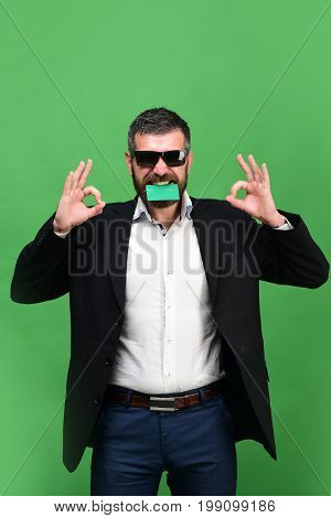 Man With Beard In Suit Holds Business Card In Teeth