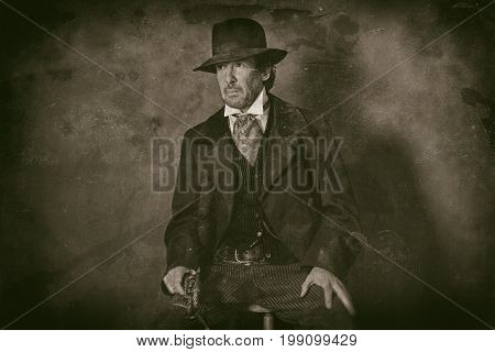 Classic Wet Plate Photo Of Vintage 1900 Western Mature Man With Revolver Sitting On Wooden Stool.