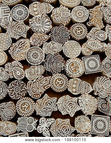 Flowers patterns sun symbols on wooden surface of mold blocks for traditional printing textile. Background from India.