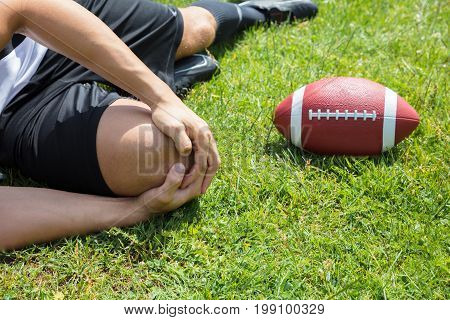 Close-up Of Male Rugby Player Suffering From Knee Injury Lying On Field