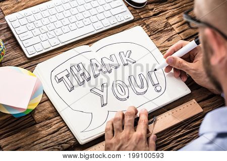 Businessman Drawing Thank You Text Speech Bubble On Notebook Over The Office Desk