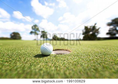 Golf ball near hole background blue sky
