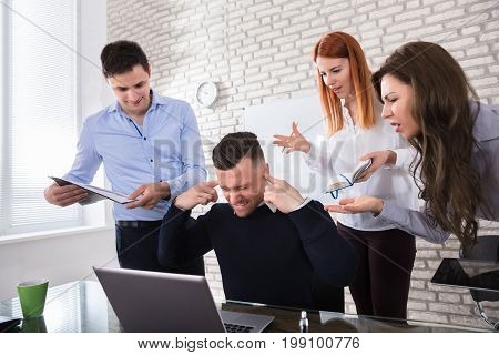 Angry Business People Pointing At Male Colleague During Meeting In Office