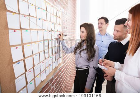 Close-up Of Business People Hands Holding Blank White Notes Notes On Corkboard