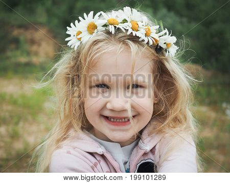 Portrait of a beautiful little girl with blond hair in a wreath of daisies. Field green grass. The child smiles happily