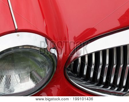 grille and headlight detail of an old red vintage sports car with chrome details