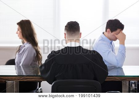 Displeased Couple Sitting In Front Of Judge At Courtroom