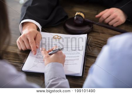 Close-up Of A Female Signing Contract On Desk In Courtroom