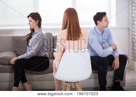 Rear View Of Female Psychologist Sitting With Young Displeased Couple