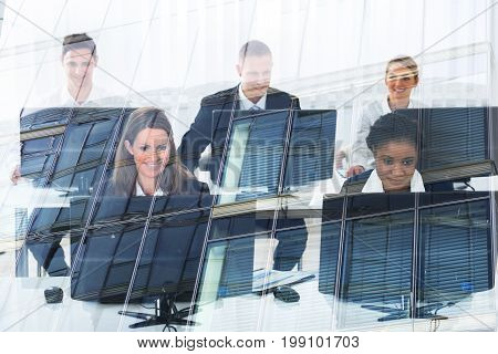 Multiethnic business people using desktop computers in office seen through glass