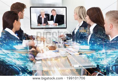 Double exposure of multiethnic business people having conference call with partners over illuminated city background