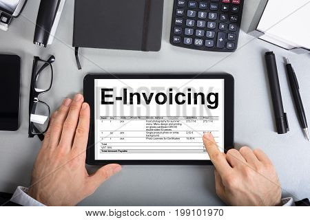Directly above shot of businessman's hands going through e-invoicing on digital tablet in office