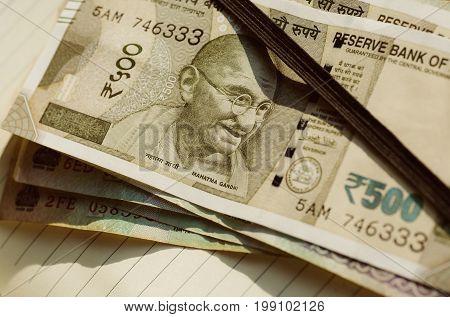 Notebook of businessman with Mahatma Gandhi face on the Indian currency notes of Rupees 500 nomination. Father of India Nation on official paper rupee currency.