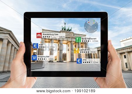 Closeup of hands holding digital tablet with various information at Brandenburg Gate