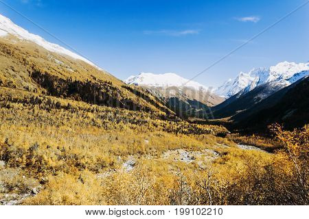 Mountains autumn landscape high peaks scenery wild nature calm scene. Lifestyle active travel hiking. Scenic scenery of wild snowy mountains and alpine valleys.