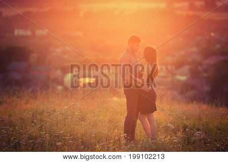 man and girl in love romantic lovers kissed, hugged sunset, sunrise against background of mountains and mist, sun, clouds in fiery red kiss, love, date.