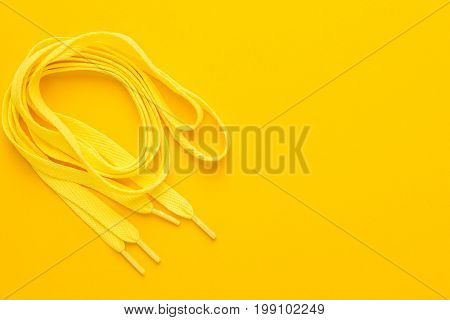 yellow sport shoe laces. shoe laces on the yellow background. sport shoe laces with copy space. top view of yellow sport shoe laces