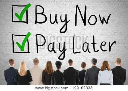 Group Of People Looking At Buy Now Pay Later Concept