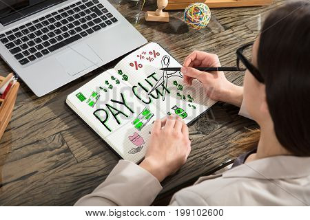 Young Woman Drawing Salary Paycut In Notepad