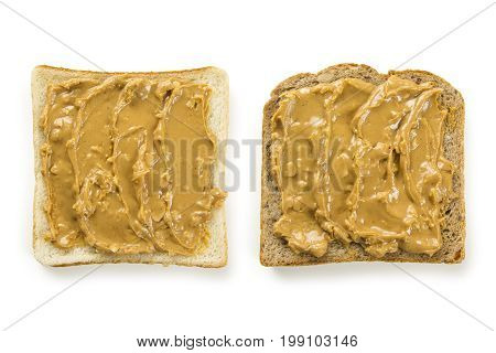 Photo of two slices of white and whole wheat bread covered in peanut butter isolated on white.