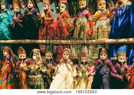 Indian market showcase with funny handmade dolls in traditional costumes. Marketplace with old style toys for children in India.