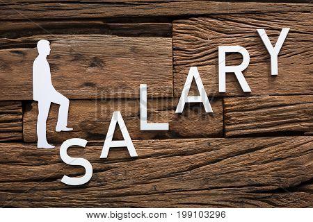 Closeup of paper businessman climbing salary ladder on wood