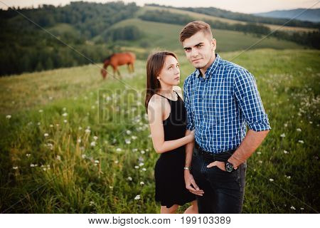 girl is holding the boyfriend of her lover, lovers are standing on the background of a horse and mountains, concept love, dates, a journey together.