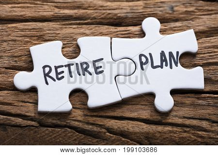 Closeup of connected retire plan jigsaw pieces on wood