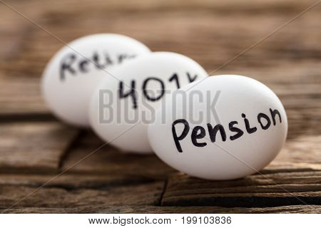 Closeup of pension 401K and retire written on white eggs