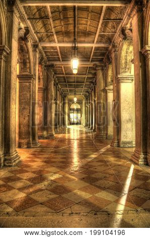 A passageway in Venice with repetitive columns and bands of light.