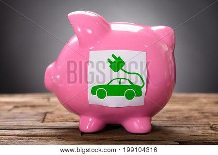 Closeup of green electric car on pink piggybank on wood