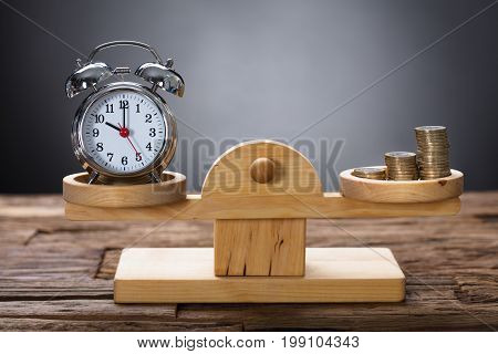 Closeup of clock and coins balancing on wooden weighing scale representing time is money concept